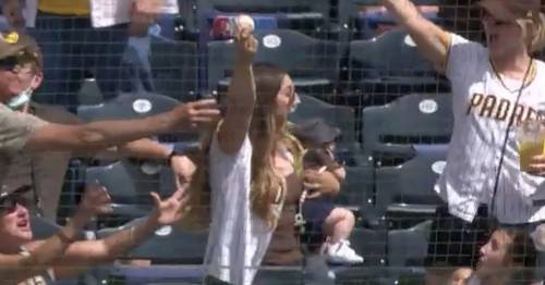 Mum catches speeding baseball while holding tiny baby as crowd roars in delight