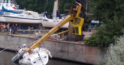Crane lowering super yacht into water topples over and crashes onto sinking boat – World News